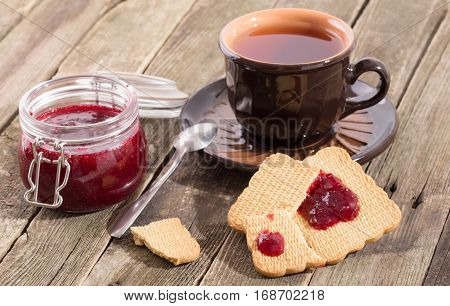Tea drinking with red berries jam and cookies. The ceramic cup with tea costs on a table from old boards the jar of jam and pieces of cookies smeared with jam nearby