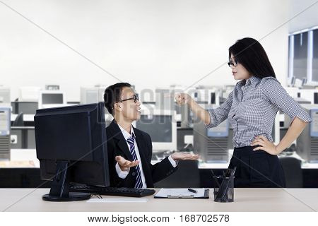 Portrait of young boss shouting to her subordinate while standing in the office