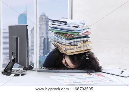 Picture of young woman sleeping on the keyboard with stack of documents over her head