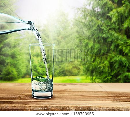 Pouring clear water into glass on nature background
