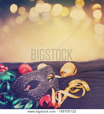 Mask with masquerade decorations border isolated on festive bokeh background with copy space, retro toned