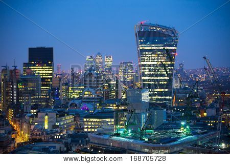 London, UK - December 19, 2015: City of London at sunset. Skyscraper Walkie-Talkie in the City of London and  business and banking aria Canary Wharf at the background