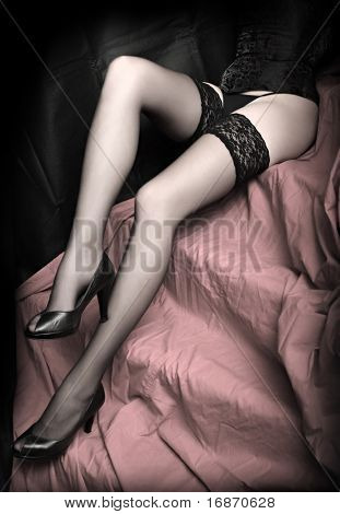 Low key studio shot beautiful slim legs in black nylons on a pink background. Great image for calendar.
