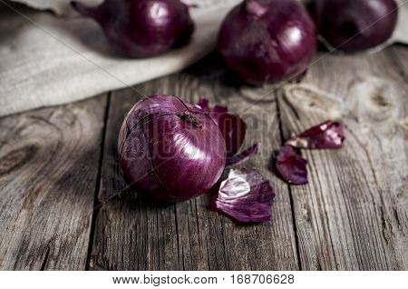 Red onions in the husk on the gray old wooden surface vintage toning