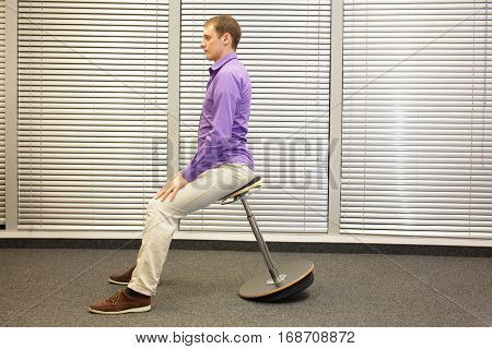 man sitting on pneumatic stool relaxing  in office