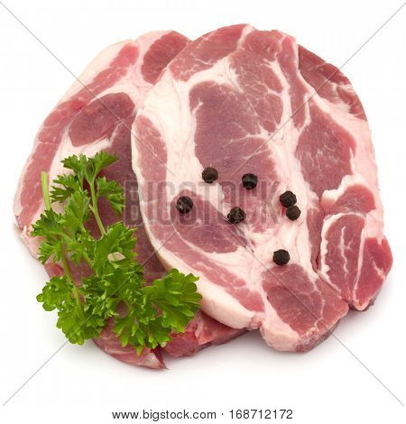 Raw pork neck chop meat with parsley herb leaves and peppercorn spices garnish isolated on white background cutout.