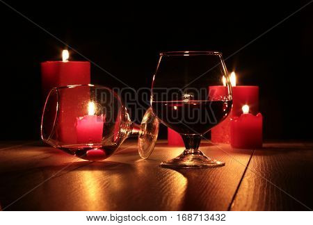 Glass of brandy or cognac and candle on the wooden table.
