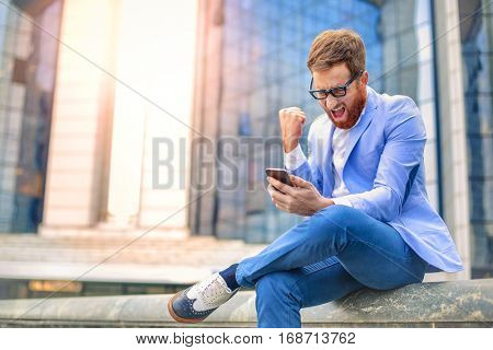 Fancy outfit on red haired man while sitting and chatting on the phone