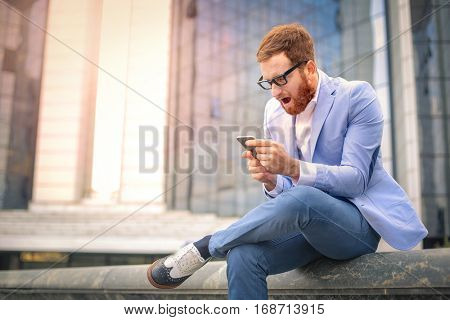 Man playing on the phone while wearing light blue suit