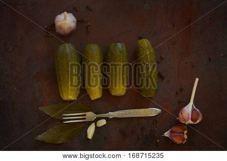 Salted cucumbers. Spices and herbs for making pickles. The top view of the wooden background