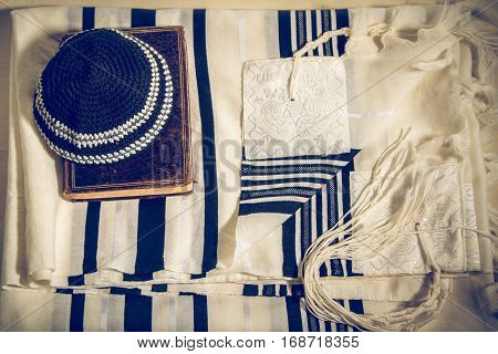 Jewish ritual objects elements of prayer vestments Kippah and Siddur jewish prayer book Talit with hebrew inscription: And brought us to Zion in joy. Toned image