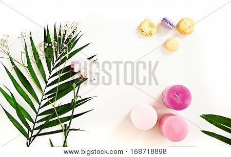 Beauty blogger flat lay on white. Green leaves and carnation flower pink ombre candles macaroons. Woman decorating ideas. Negative space for text