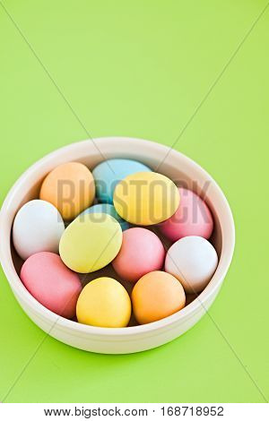 Colorful decorated eggs on a white plate and greenery background. Easter card. Negative space