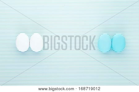 Pair of white and light blue eggs on a colorful striped backdrop. Creative design minimal concept. Negative space