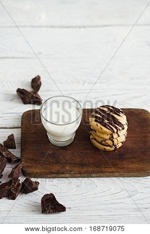Glass of milk and shortbread butter cookies and dark chocolate chunks. White wooden background. Minimalist food photography