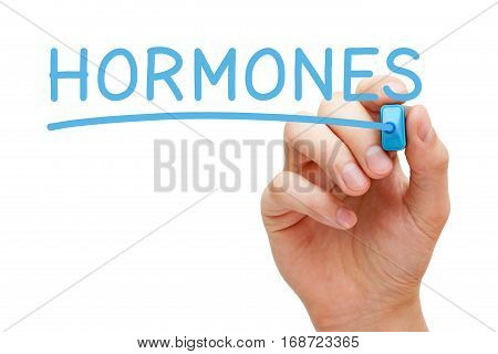 Hand writing Hormones with blue marker on transparent glass board.