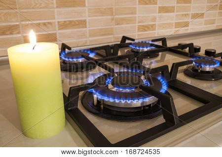 Closeup shot of blue fire from domestic kitchen stove. Gas cooker with burning flames propane gas and candle. Old and new concept