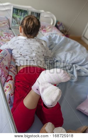Little girl lying in bed and watching movies with a laptop in his bedroom. She is wearing walking socks