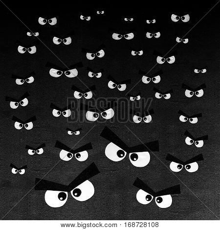 Crowd of angry eyes on dark gray background. Pattern of many human cute eyes are visible in the dark night. Strange scary eyes in the dark.