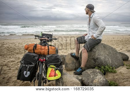 Long Distnace Cyclist With Bicycle On Beach