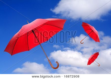 Three red umbrellas flying in a rich blue sky. Conceptual image.