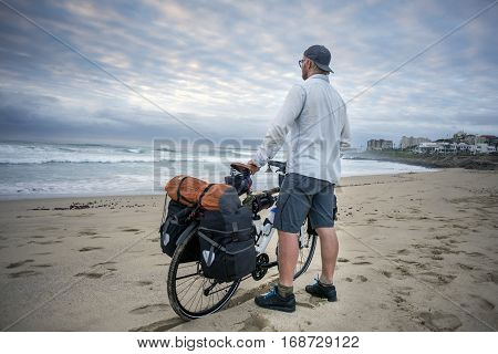 Young Man With Packed Bicycle On Beach