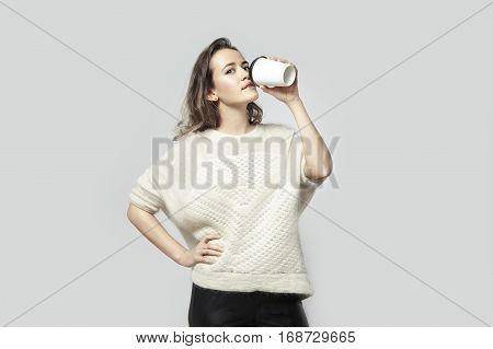 Blonde beautiful hipster woman wearing white sweater drinking coffee from paper cup. Disposal package to take away girl isolated studio shot.