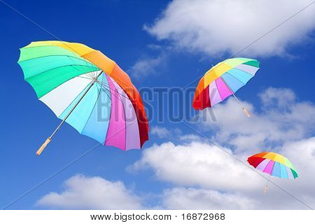 Three rainbow umbrellas flying in a rich blue sky. Conceptual image.