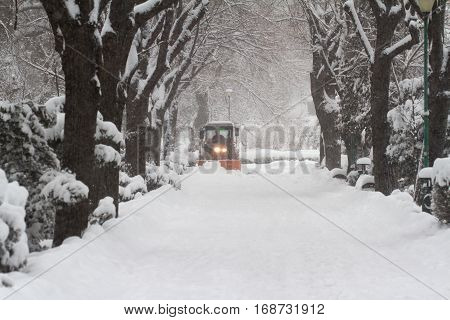 orange tractor with headlights driving down snow in a park alley in the middle of winter snowfall