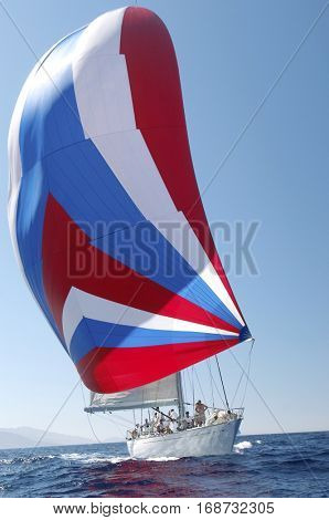 Boat with colorful sail in yacht race against the clear blue sky