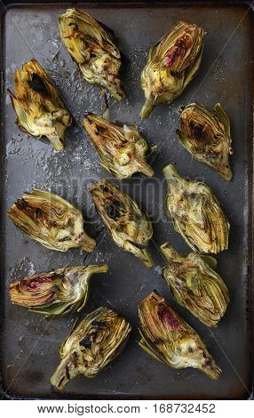 High angle view of grilled artichoke halves on a baking sheet.