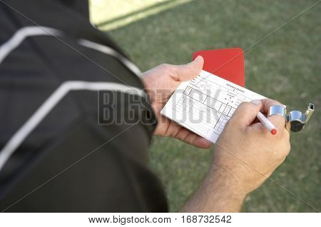 Mature referee writing in his report book while holding a red card