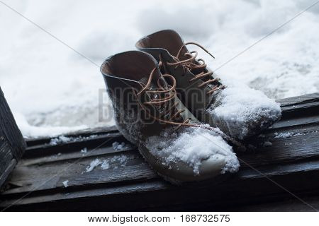 top view of a pair of vintage brown leather shoes by the house wooden open door entrance covered in snow in winter time