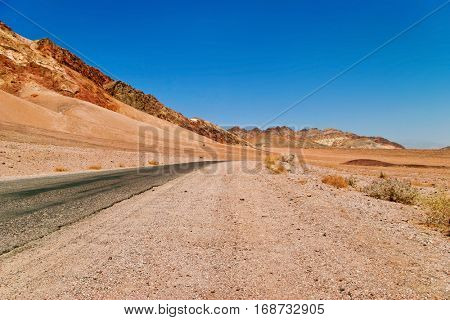 Lifeless landscape with road. Death Valley. California. USA