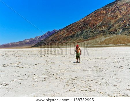 Badwater basin in Death Valley National Park, California, USA with walking photographer