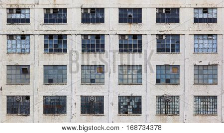 Windows in a facade of an old neglected factory building