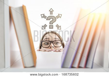 Short curious white girl trying to see what book there are on a library shelf. She wants to find answers to her questions