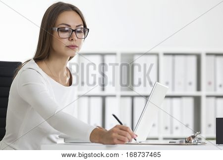 Side View Of A Woman In Glasses Writing