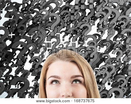 Close up of a woman's head against black question marks background. Concept of multiple questions that need to be answered.