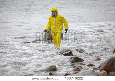 scientist in protective suit with silver case walking on rocky beach