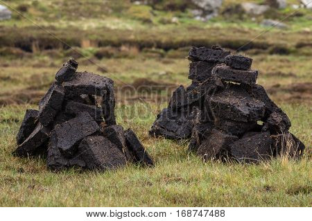 North Coast Scotland - June 6 2012: Closeup of two short stacks of blocks of black peat the local fuel. Heaps on green-brown grassy field.