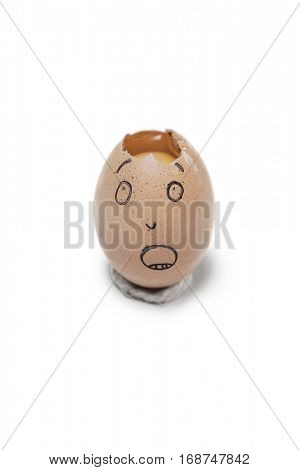 Broken egg with face drawn on it over white background
