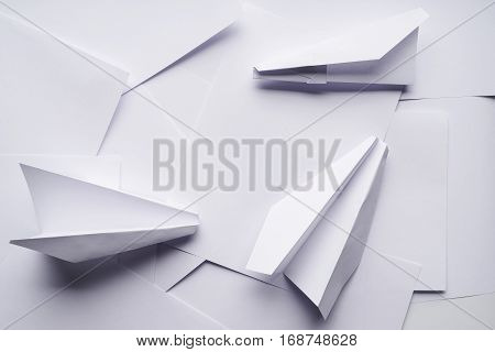 White paper planes on a background sheet of office paper