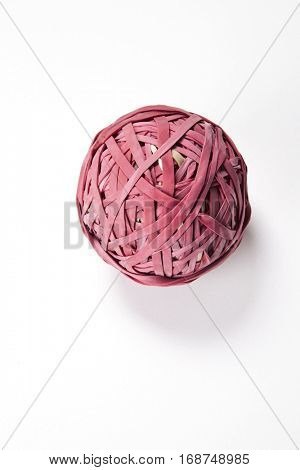 Close-up of rubber band ball over white background