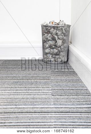 Wastebasket full of crumpled paper in corner on carpet floor in room
