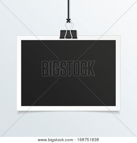Retro photo frame mockup. White plastic border hanging on a clip on a light background. Realistic detailed Photo icon design template. Empty snapshot for your design. Vector illustration. EPS 10.