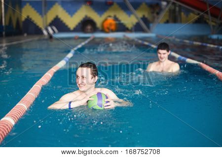 man in the pool water recklessly playing football