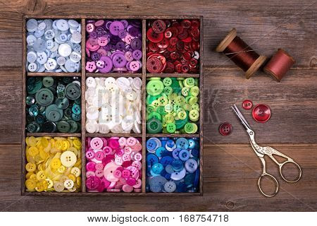 A box of colourful buttons, sorted into colour groups, in an old wood box. Spools of thread, a needle and embroidery scissors are placed to one side. Needlecraft and scrapbooking theme.