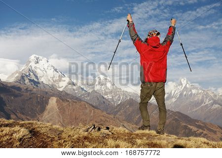 Elated And Blissful Young Hiker Cheering With His Arms Raised In The Sky After Trekking In Highlands