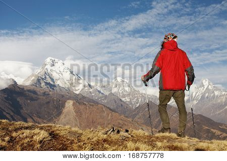 Back Shot Of Young Hiker With Trekking Poles Standing On Edge Of Cliff In Front Of Amazing Scene Of